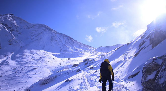 Скиор засне леден ореол около Слънцето над Швейцарските Алпи